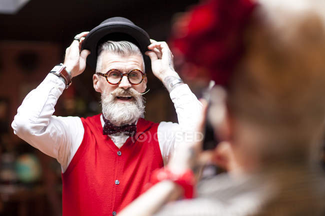 Странная винтажная женщина фотографирует парня примеряющего шляпу в антикварной лавке — стоковое фото