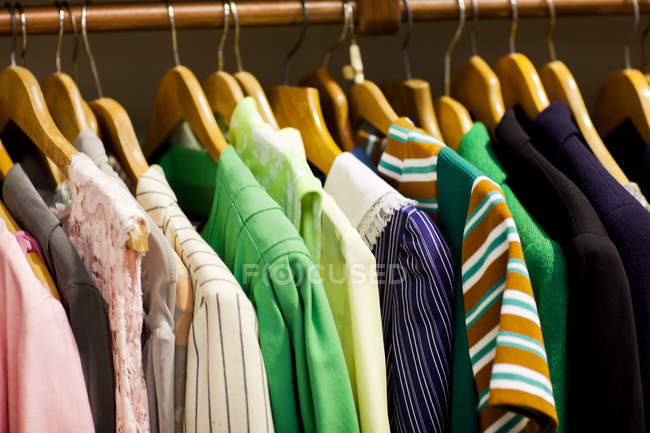 Vintage clothes on clothes rail in antique and vintage emporium — Stock Photo