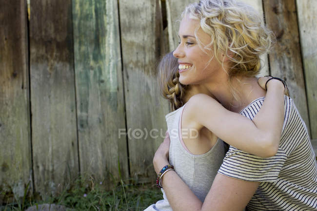 Mother and daughter hugging, wooden fence in background — Stock Photo