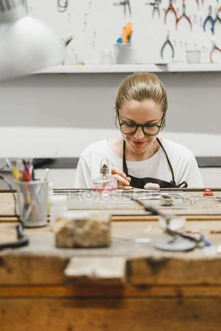 Front view of Female jeweler working with miniature hand tool at workbench — Stock Photo
