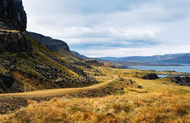 Довгий грунтовій дорозі вздовж скелястому узбережжі — стокове фото