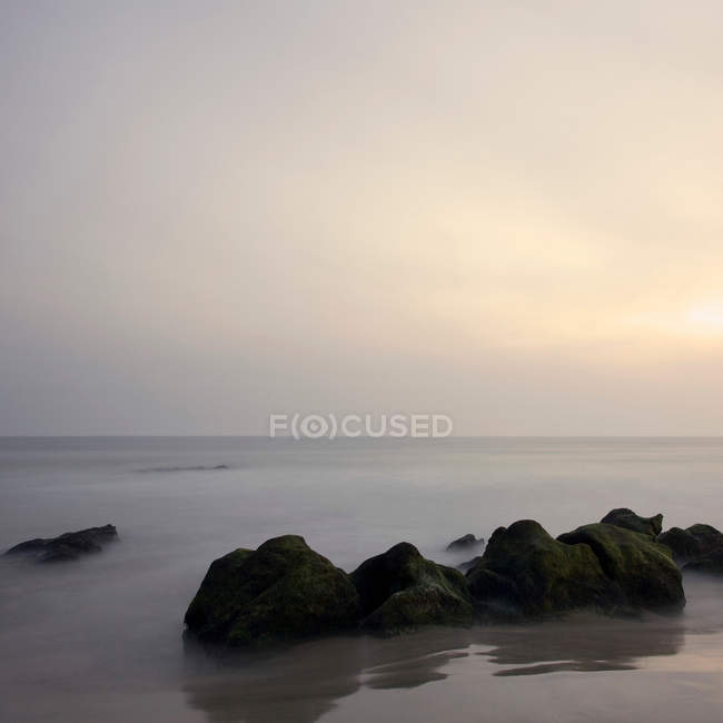 Rocks in calm sea at beautiful foggy sunrise — Stock Photo