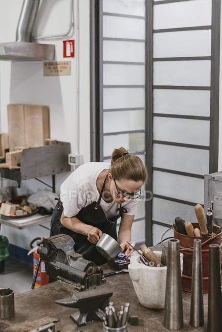 Vista in lontananza del gioielliere femminile che versa il liquido nello stampo gioielli al banco da lavoro — Foto stock
