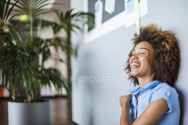 Young woman with afro hair laughing with eyes closed — Stock Photo