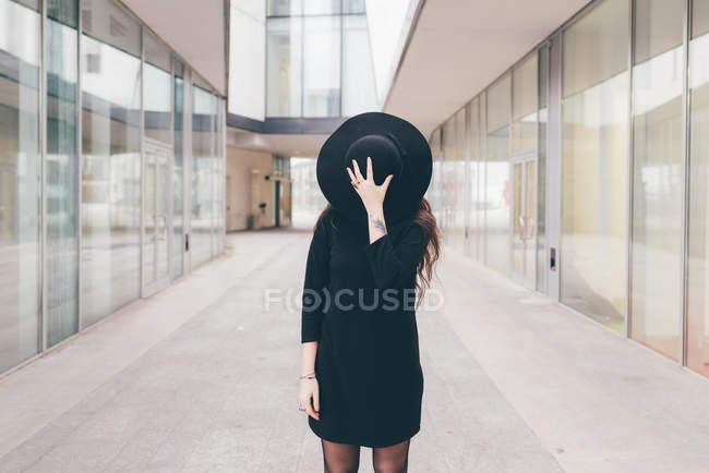 Retrato de mujer joven en ambiente urbano, cubriendo la cara con sombrero - foto de stock
