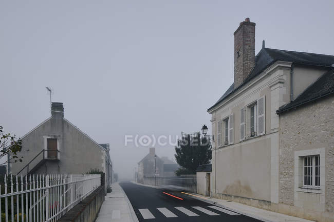 Taillight trail on road through Meigne-le-Vicomte village on misty morning, Loire Valley, France — Stock Photo