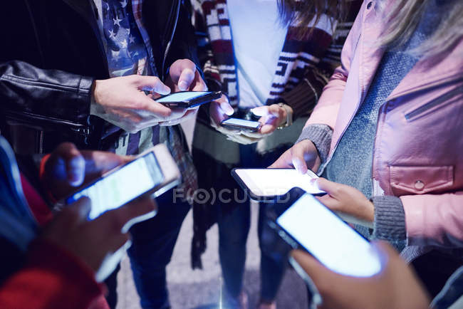 Mid section of young adult friends standing in circle looking at smartphones — Stock Photo