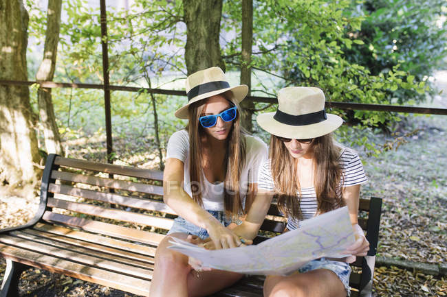 Two young female friends sitting on bench looking at map in park — Stock Photo