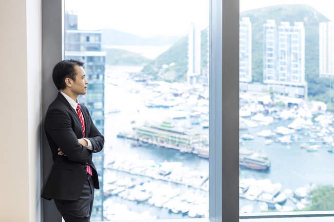 Uomo d'affari che guarda dalla finestra dell'ufficio sul porto — Foto stock