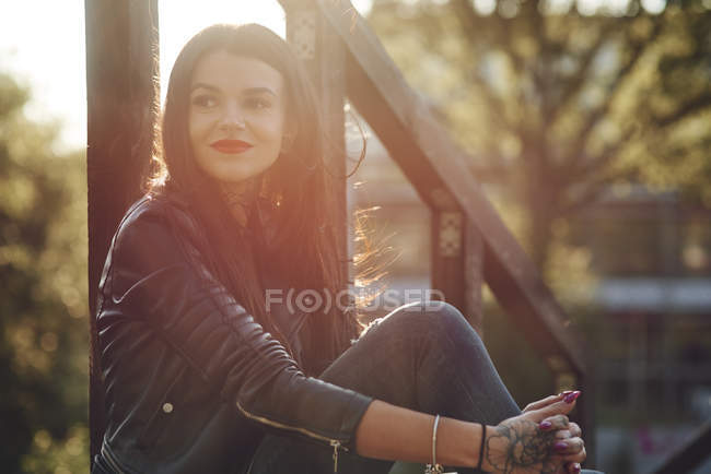 Mujer joven relajándose al aire libre, tatuajes en las manos - foto de stock