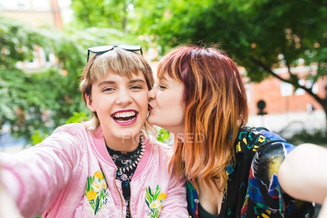 Dois retro estilo mulheres jovens tomando selfie no parque — Fotografia de Stock