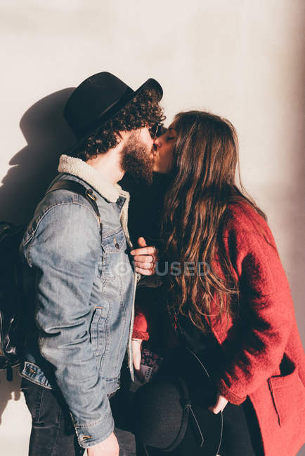 Young couple standing against wall, kissing — Stock Photo