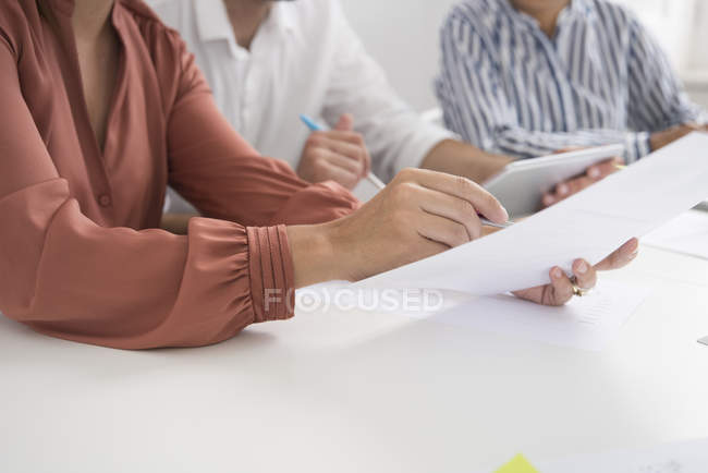 Cropped shot of businesswomen and man with paperwork and digital tablet boardroom table — Stock Photo