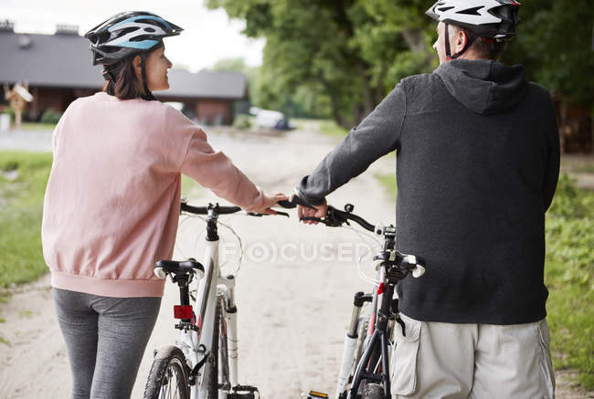 Rear view of mature couple walking with bicycles — Stock Photo
