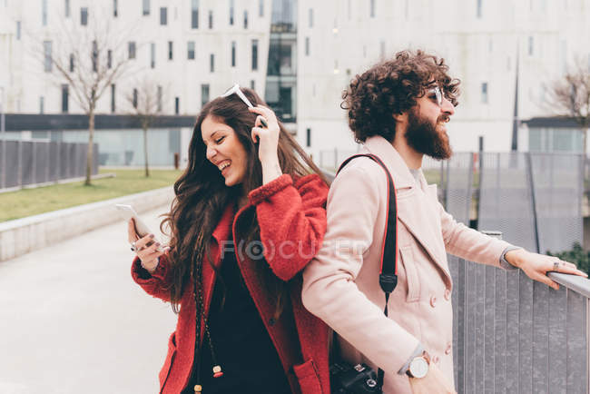Young couple outdoors, young woman looking at smartphone, laughing — Stock Photo