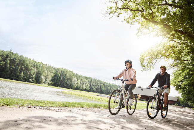 Mature couple cycling beside lake — Stock Photo