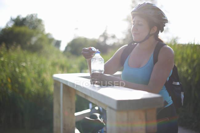 Велосипедистка берет перерыв и держит бутылку с водой — стоковое фото
