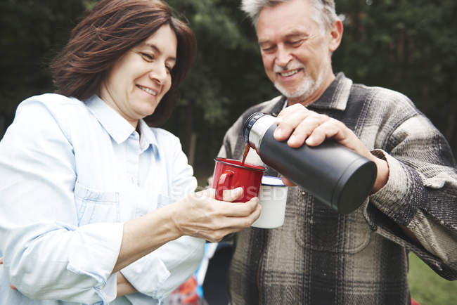 Mature couple pouring hot drink from drinks flask — Stock Photo