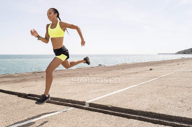 Young woman running outdoors and jumping over gap in bridge — Stock Photo