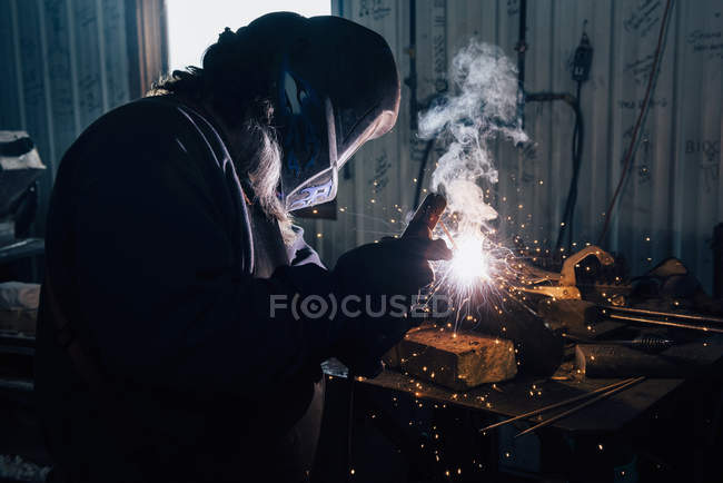 Blacksmith in welding mask welding metal in workshop — Stock Photo