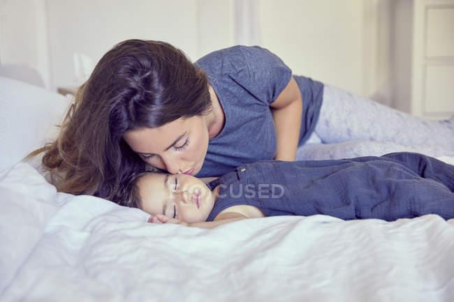 Mãe da criança brincando de dormir na bochecha — Fotografia de Stock