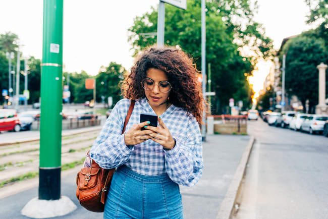 Жінка за допомогою мобільного телефону в центральний застереження на вулиці, Мілан, Італія — стокове фото