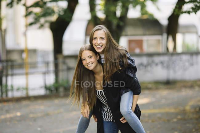 Porträt der jungen Frau geben bester Freund ein Huckepack im park — Stockfoto