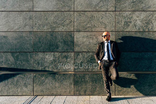 Mature businessman leaning against wall — Stock Photo