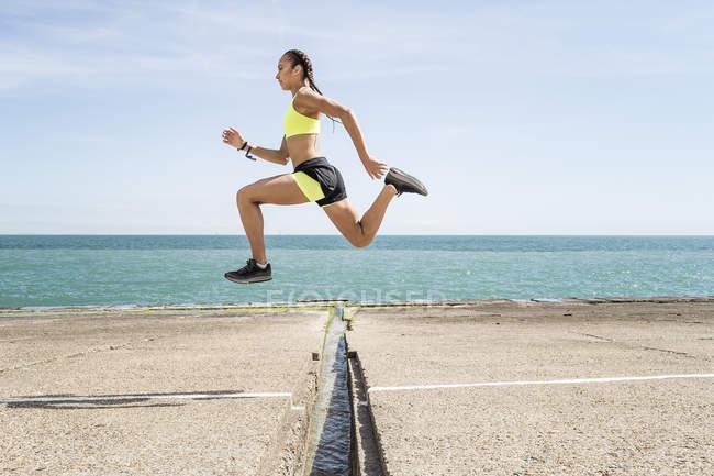 Seitenansicht der Frau Läufer über Lücke in der Brücke springen — Stockfoto