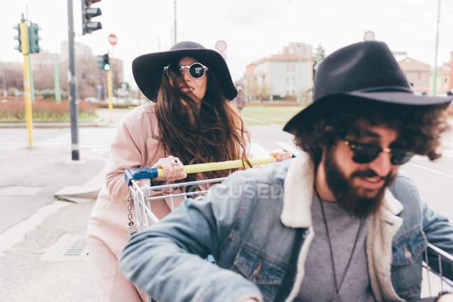 Young couple outdoors, woman pushing man along in shopping trolley — Stock Photo