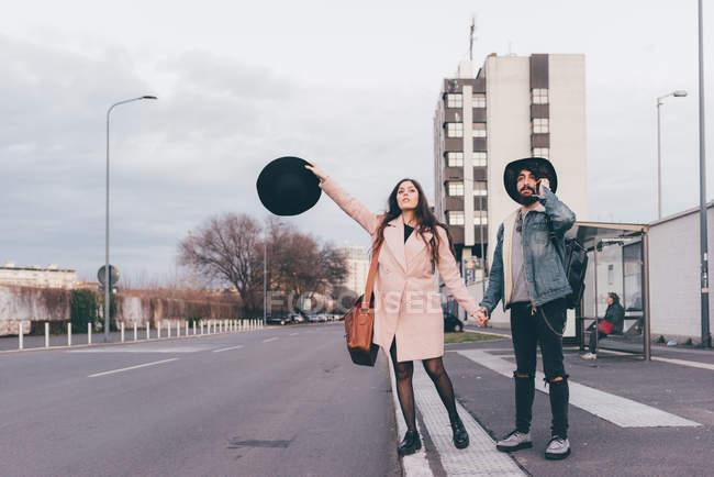 Junges Paar im Freien, Händchen haltend, junge Frau mit Hut in der Hand — Stockfoto