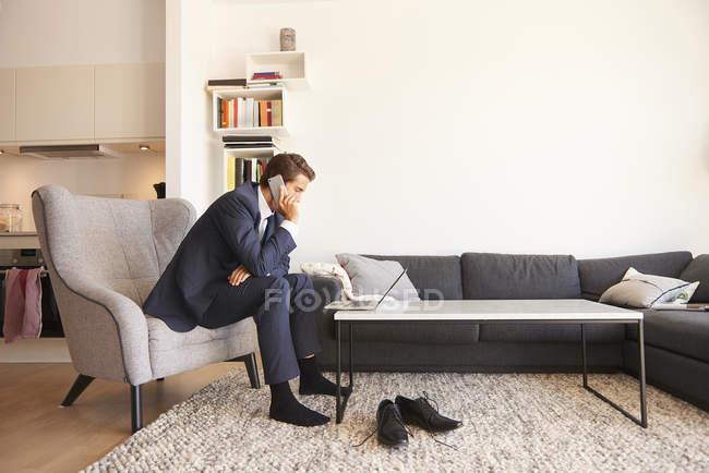 Бизнесмен с помощью ноутбука и делая смартфон вызов в гостиной — стоковое фото
