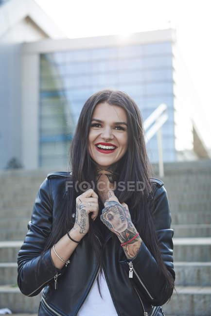 Портрет молодой женщины, держащей воротники куртки, улыбающейся, татуировки на руках — стоковое фото