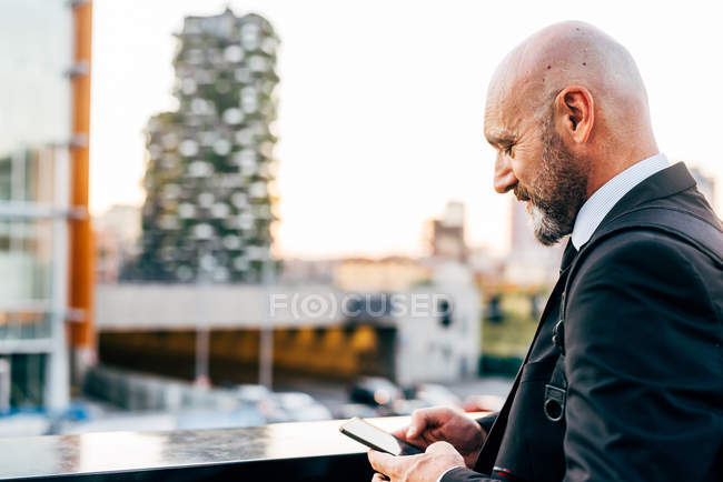Homme d'affaires mature utilisant un smartphone en plein air — Photo de stock