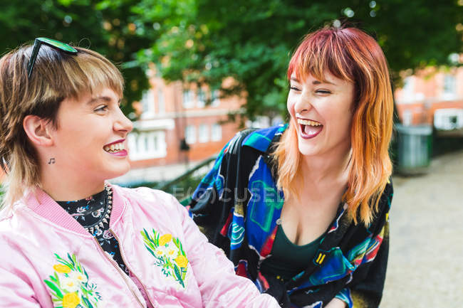 Two retro styled young women laughing in park — Stock Photo
