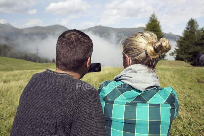 Rear view of couple in field photographing mist, Tirol, Steiermark, Austria, Europe — Stock Photo