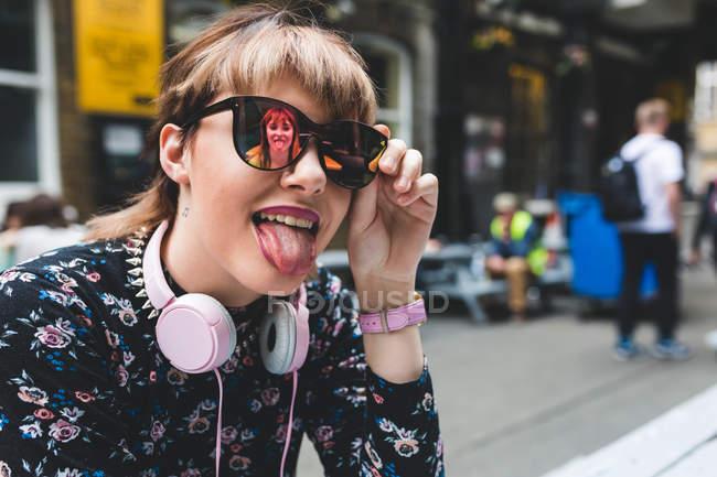 Giovane donna con gli occhiali da sole che sporge la lingua — Foto stock