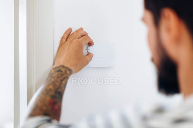 Man turning dimmer switch — Stock Photo