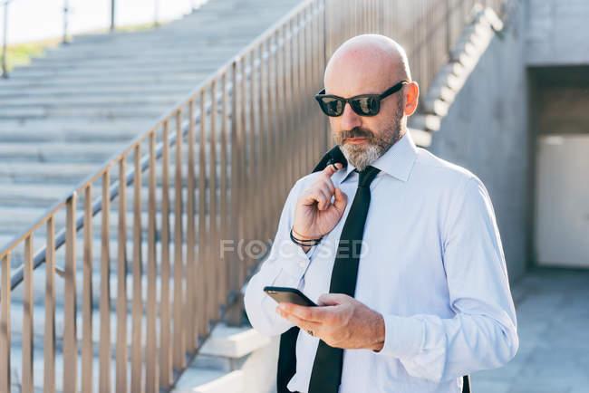 Uomo d'affari maturo portando giacca a spalla e utilizzando smartphone — Foto stock