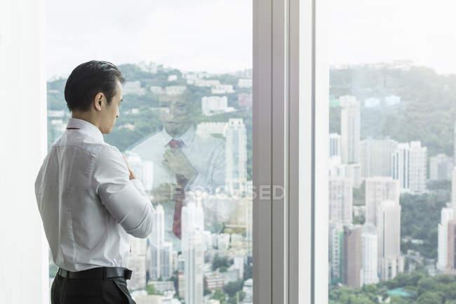 Бизнесмен, выглядывающая в окно — стоковое фото