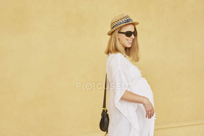 Portrait of pregnant woman against yellow wall — Stock Photo