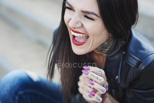 Портрет молодой женщины со смехом, татуировки на шее и руке — стоковое фото