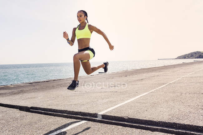 Junge Frau läuft ins Freie und springt über Brückenspalt — Stockfoto