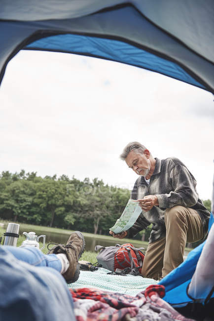 Mature woman relaxing in tent while man outside looking at map — Stock Photo