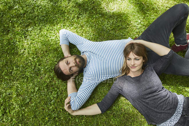 Visão aérea do casal deitado na grama — Fotografia de Stock
