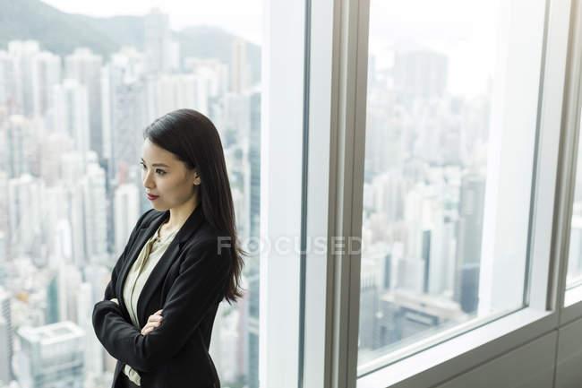 Бізнес-леді, зброї схрещені, дивиться з вікна — стокове фото