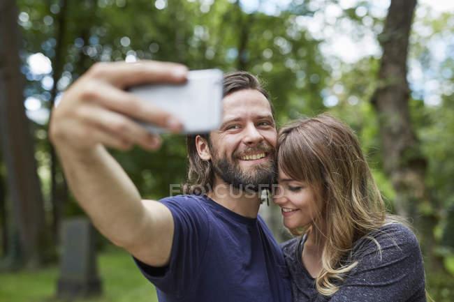 Couple souriant et selfie prise dans le parc — Photo de stock