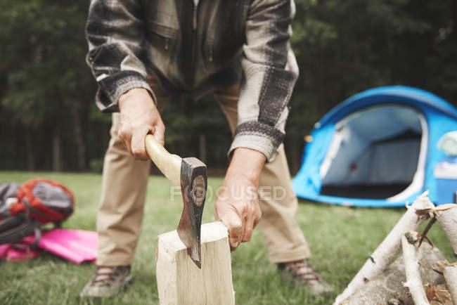 Homme utilisant la hache pour couper le bois de chauffage — Photo de stock