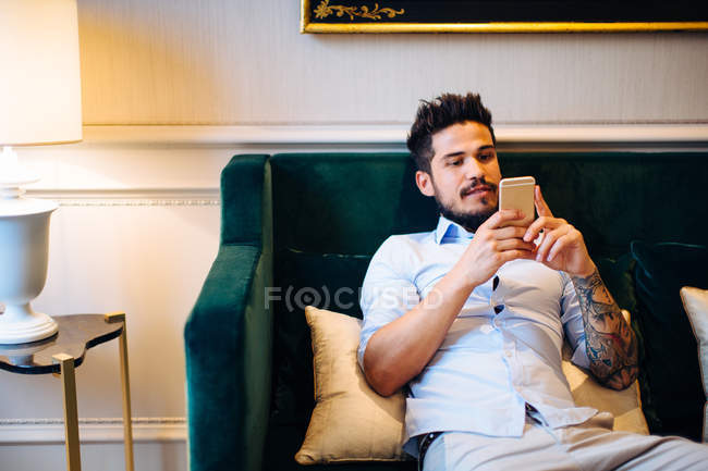 Людина сутулість на дивані готель за допомогою мобільного телефону — стокове фото