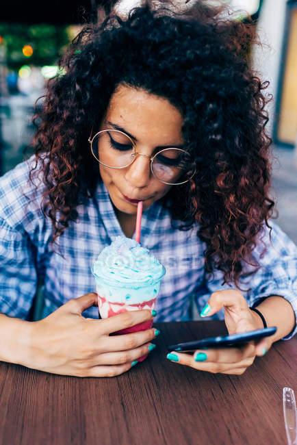 Woman using mobile phone while enjoying icy drink — Stock Photo